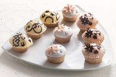 Glasade muffin med dekorativ blom- toppning Arkivbild