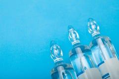 Glasampullen met antibiotica op een blauwe achtergrond stock foto's
