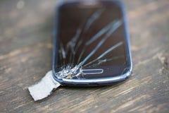 Glasanzeige des defekten Telefons auf dem Tisch Stockbild