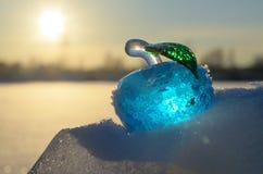 Glasapfel auf Schnee. Stockbild
