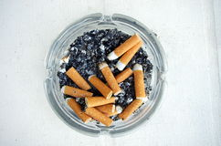 Glasaschenbecher mit Zigarettenkippen Lizenzfreies Stockfoto