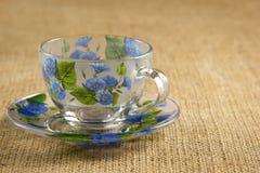 Glasbecher auf einer Untertasse für Tee mit blauen Blumen Lizenzfreie Stockfotos