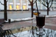 Glasbecher mit braunem, geschmackvollem, heißem, wohlriechendem, alkoholischem Glühwein mit einer Scheibe der Zitrone und einem S Stockfotos
