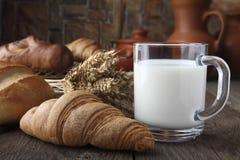 Glasbecher mit den Milch-, Brötchen- und Bäckereiprodukten, die auf einer alten Tabelle auf dem Hintergrund von Weizenspitzen und Stockbild