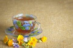 Glasbecher Tee mit den gelben und blauen Blumen Stockbilder