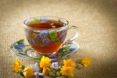 Glasbecher Tee mit den gelben und blauen Blumen Lizenzfreies Stockbild