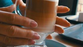 Glasbeker met koffie, van donker bruin aan melkachtig wit wordt gesorteerd dat Mooie latte met een groot schuim in de koffie Een  stock video