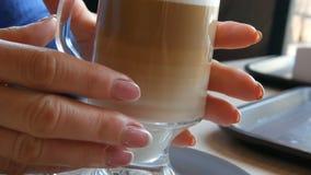 Glasbeker met koffie, van donker bruin aan melkachtig wit wordt gesorteerd dat Mooie latte met een groot schuim in de koffie Een  stock videobeelden