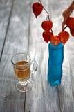 Glasbier auf hölzernem Hintergrund Physalis Stockfoto