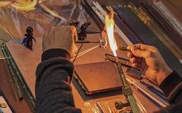 Glasblåsaren gör en statyett av exponeringsglas Smältande exponeringsglas på en gasgasbrännare royaltyfri fotografi