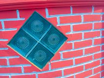 Glasblöcke auf dem Wandhintergrund des roten Backsteins Quadratischer Glasblock Stockfotografie