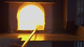 Glasblazer in zijn workshop die de staaf met vloeibaar glas nemen uit gloeiende hete oven Close-up stock video