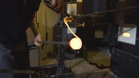 Glasblazer in zijn workshop die de staaf met vloeibaar glas nemen uit gloeiende hete oven stock video