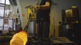 Glasblazer in zijn workshop die staaf met vloeibaar glas nemen en het draaien Close-up stock footage