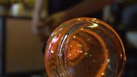 Glasblazer in zijn workshop die staaf met vloeibaar glas nemen en het draaien Close-up stock video