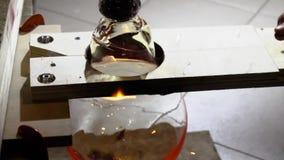 Glasblazer in zijn workshop die staaf met vloeibaar glas nemen en het draaien Close-up Langzame Motie stock video
