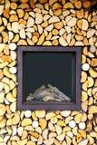 Glasdeur met ijzerrand van een openluchtfornuis door gehakte zeer keurig gestapelde logboeken stock foto