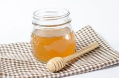 Glasdose Honig mit einem hölzernen Honigschöpflöffel Lizenzfreie Stockfotos