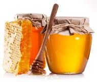 Glasdosen voll des Honigs, der Bienenwaben und des hölzernen Stockes Lizenzfreie Stockfotos
