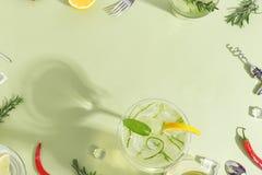 Glasdrinkbeker met komkommerwater, een fles en een fruit op een lichtgroene achtergrond Minimalistic creatief concept De ruimte v stock foto