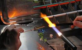 Glaser mit der Gasfackel bei der Mischung einer Glasplatte 5 beleuchtet Stockbild