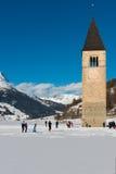 Glasera sjön Resia med snö och den gamla kyrktorn i en solig dag, Curon Venosta, Italien Royaltyfri Bild