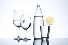 Glasföremål och flaskan fyllde med vatten på vit bakgrund Arkivbild