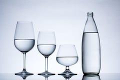 Glasföremål och flaskan fyllde med vatten på vit bakgrund Royaltyfri Foto