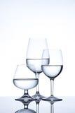 Glasföremål och flaskan fyllde med vatten på vit bakgrund Royaltyfria Bilder