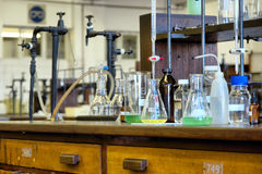 Glasföremål på trätabeller i kemisk labb Royaltyfri Fotografi