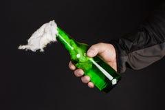 Glasflasche, der so genannte Molotowcocktail in der Hand von Stockfotos