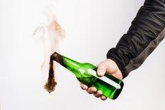 Glasflasche, der so genannte Molotowcocktail in der Hand von Stockfoto