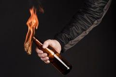 Glasflasche, der so genannte Molotowcocktail in der Hand von Stockbild