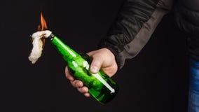 Glasflasche, der so genannte Molotowcocktail in der Hand von Stockbilder