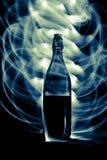 Glasflasche mit Funken und Lichtwellen Stockbilder