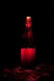 Glasflasche mit Funken und Lichtwellen Stockbild