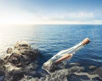 Glasflasche mit Mitteilung in Meer Stockfotos