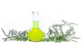 Glasflasche mit reinem Extraolivenöl und Ölzweigen Olivenbaumbrunch mit den Oliven lokalisiert auf weißem Hintergrund Stockbilder