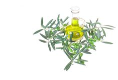 Glasflasche mit reinem Extraolivenöl und Ölzweigen Olivenbaumbrunch mit den Oliven lokalisiert auf weißem Hintergrund Stockfotografie