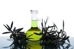 Glasflasche mit reinem Extraolivenöl und Ölzweigen Olivenbaumbrunch mit Oliven Stockfotos