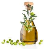 Glasflasche Olivenöl mit Niederlassung von Oliven Stockfoto