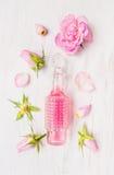 Glasflasche rosa Rosenwasser auf weißem hölzernem Hintergrund mit der Knospe und dem Blumenblatt Stockfotografie