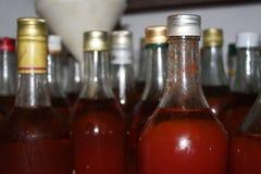 Glasflasche Tomatensaft mit vielen anderen unscharfen Flaschen Lizenzfreie Stockfotografie
