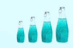 Glasflaschen mit Basilikum LED der blauen Farbe der verschiedenen Größen stehen auf einem blauen Hintergrund lizenzfreie stockfotos