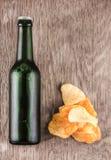 Glasflaska av öl och chiper Royaltyfria Bilder