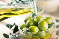 Glasflaska av högvärdig jungfrulig olivolja och några oliv med le arkivbild