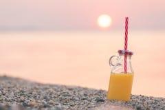 Glasflaska av ny orange fruktsaft på stranden på solnedgången över havet Royaltyfria Bilder