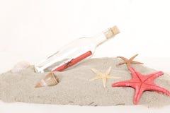 Glasflaska med anmärkningen inom på sand arkivbild