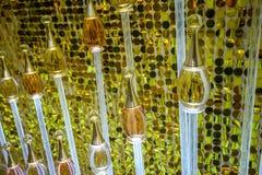 Glasflaska med det guld- lyxiga locket på genomskinligt akrylrör ag royaltyfri fotografi