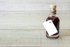 Glasflaska med en mörk flytande Fotografering för Bildbyråer